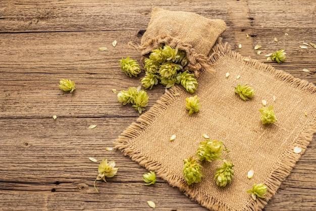 Whole hops in bag on wooden old table. brewery. beer ingredients. sack of hops on vintage boards