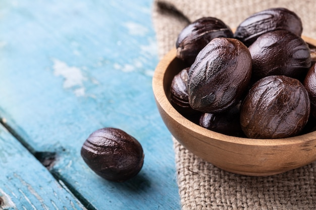 Whole inshell nutmeg nuts in a bowl on blue rustic wooden table.