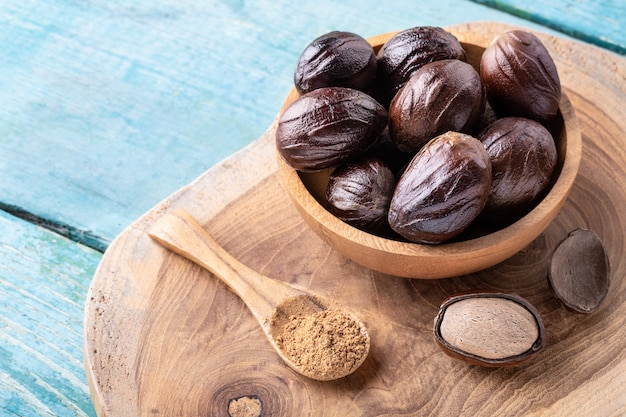 Whole inshell nutmeg nuts in a bowl and a spoon with nut powder on blue rustic wooden table.