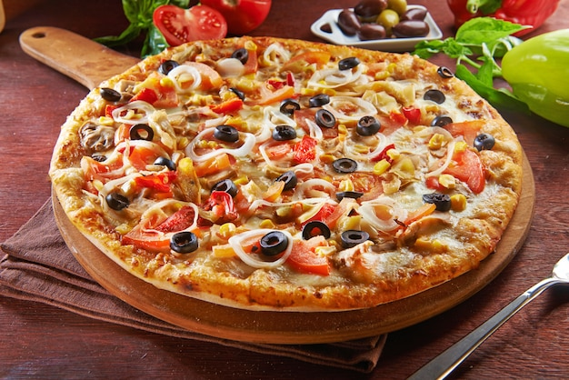 Whole italian pizza on wooden table with ingredients