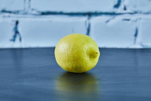 Whole juicy yellow lemon on blue surface
