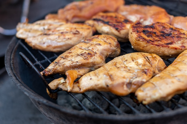 Whole large pieces of chicken meat are grilled