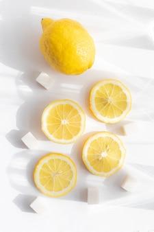 Целый лимон и нарезанный лимон на белом фоне