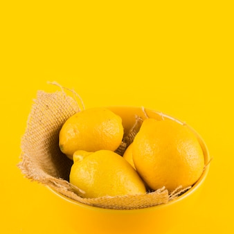 Whole lemon in bowl against yellow backdrop