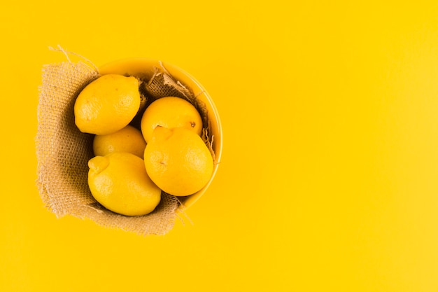 Whole lemons in the bowl with jute fabric on yellow background