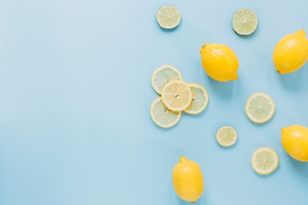 Whole lemons near slices citruses