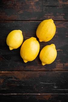 텍스트 복사 공간이 있는 오래된 어두운 나무 테이블 배경에 전체 레몬 세트