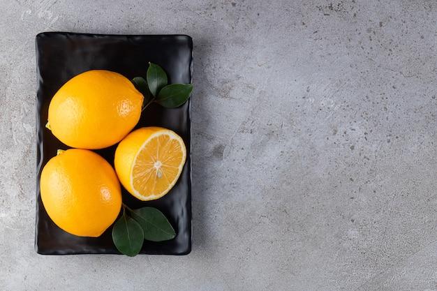 Целые лимоны с листьями на черной тарелке