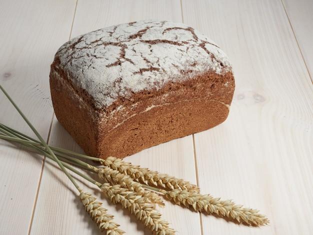 Целый буханка ржаного хлеба на светлом деревянном фоне