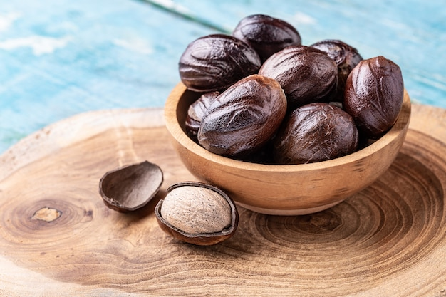 Whole nutmeg nuts in a bowl on blue rustic wooden table.