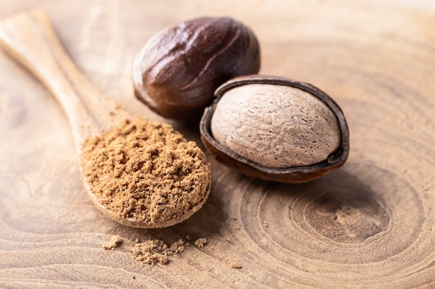 Whole nutmeg nuts and a spoon with nut powder on rustic wooden table close-up.