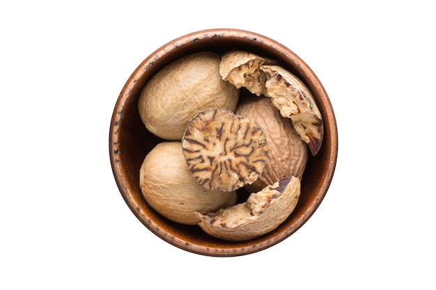Whole nutmeg spice in wooden bowl, isolated on white background. seasoning top view