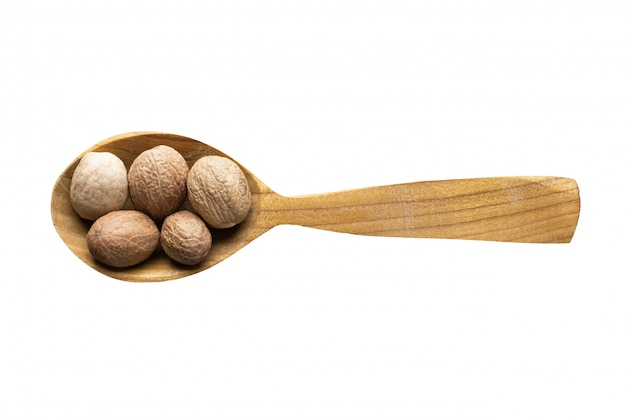 Whole nutmeg in wooden spoon isolated on white background.