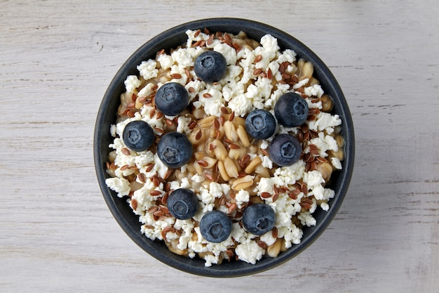 Whole oat porridge with blueberries, flax seeds and cottage cheese on a white wooden table