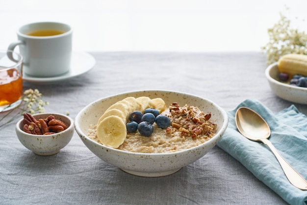 Whole oatmeal, large bowl of porridge with banana, blueberries, nuts for breakfast,