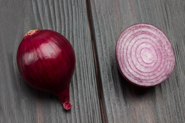 玉ねぎ全体と玉ねぎ半分。紫玉ねぎ。暗い木の背景。上面図