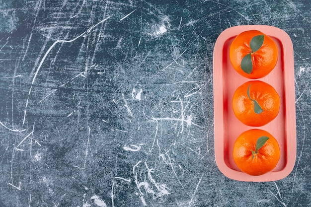 Целые оранжевые плоды с зелеными листьями на розовой тарелке.