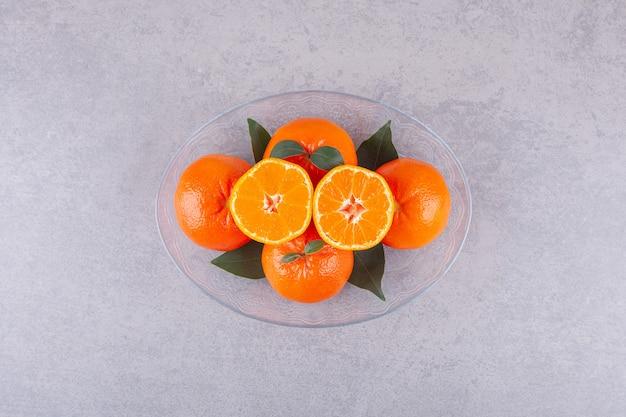 Целые плоды апельсина с нарезанным мандарином на каменной поверхности.