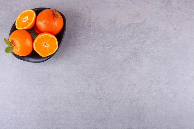 Whole orange fruits with sliced tangerines placed in black bowl.