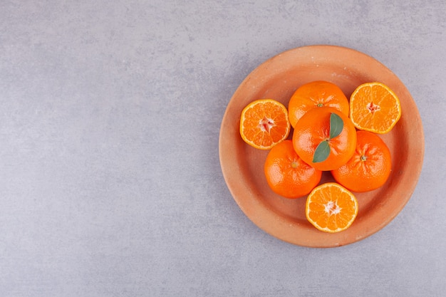 Whole orange fruits with sliced tangerines placed on clay plate.