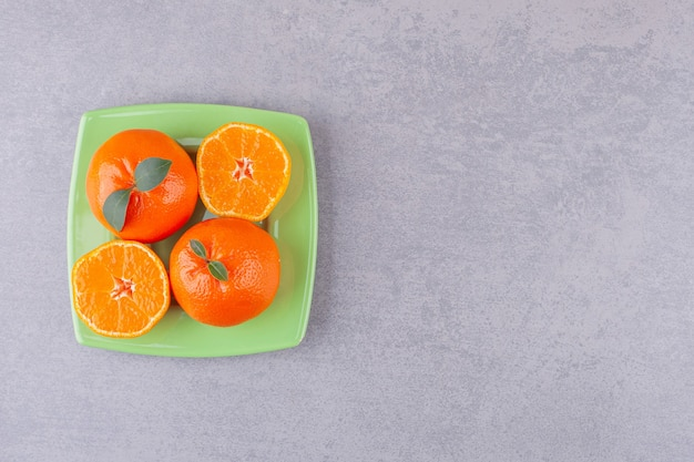 Whole orange fruits with sliced tangerines placed on green plate.