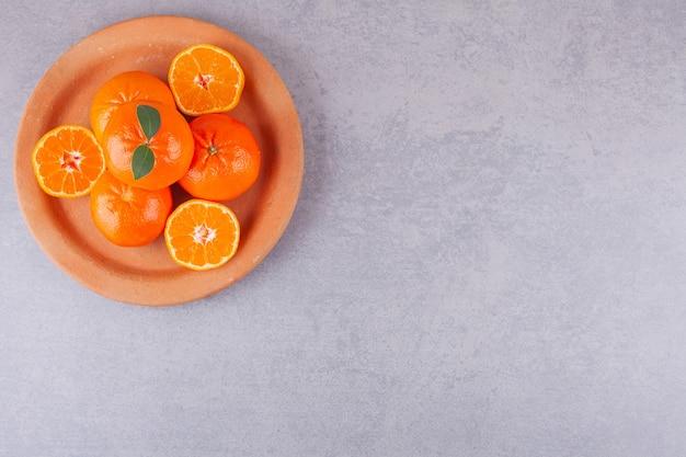 Целые плоды апельсина с нарезанными мандаринами на глиняной тарелке.