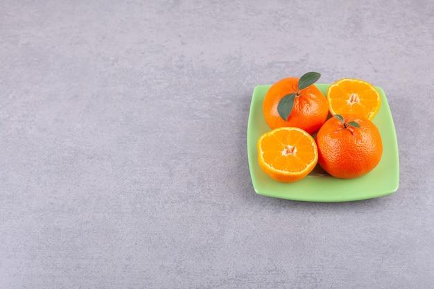 Целые оранжевые плоды с нарезанными мандаринами на зеленой тарелке.