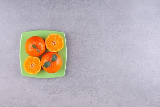 얇게 썬 감귤과 전체 오렌지 과일은 녹색 접시에 배치됩니다.