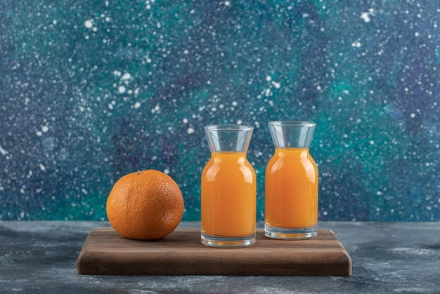 Intera arancia e succo su tavola di legno.
