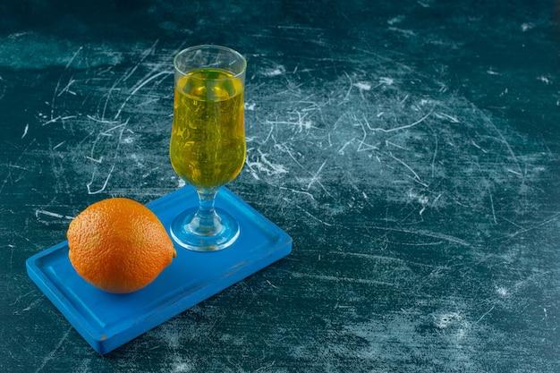 Целый апельсин рядом с деревянной тарелкой фруктового сока, на синем фоне.