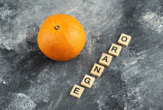 Whole orange with wooden letters spelled as orange.