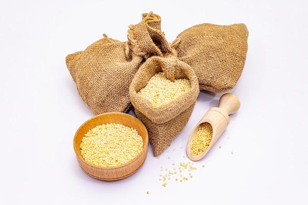 白い背景で隔離の全皮をむいたキビの穀物