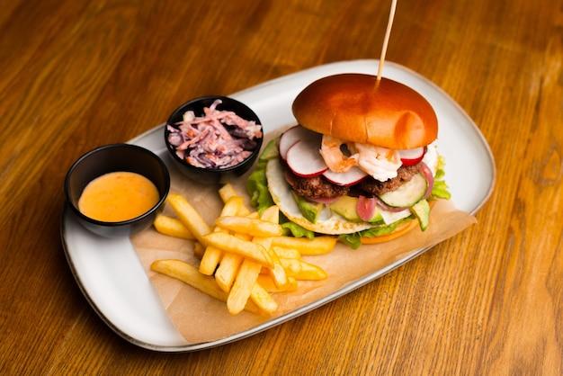 Цельное изображение бургера на белой тарелке, на нем тоже немного картошки фри.