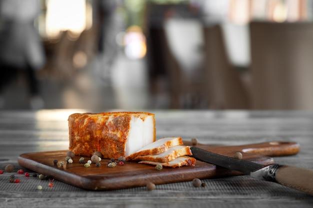 Целый кусок копченого или соленого сала, перец, чеснок на деревянной разделочной доске