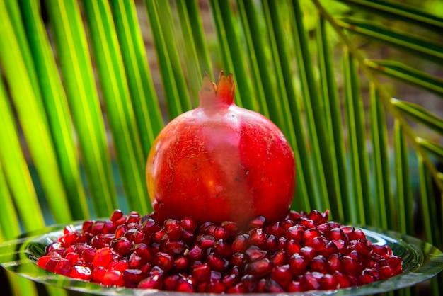 Весь гранат и семена на зеленых пальмовых листьев. органические био фрукты, еда на отдыхе в тропических странах