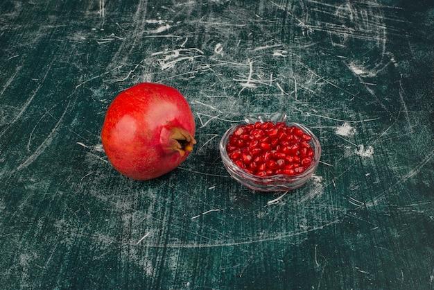 Целый гранат и семена на мраморном столе.