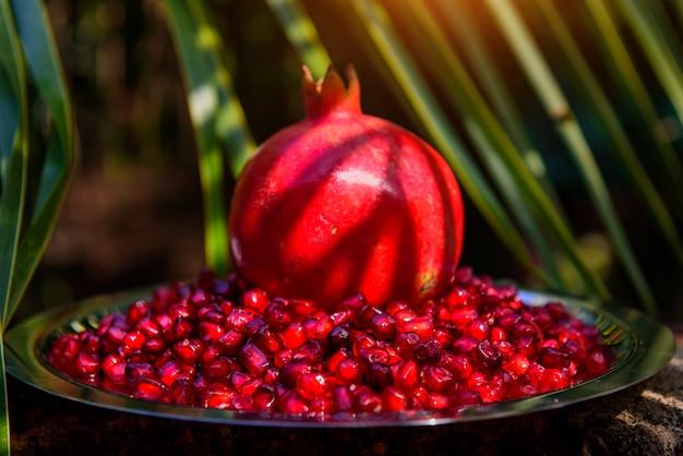 Весь гранат в середине спелых семян граната против пальмовых листьев. натюрморт с фруктами граната. пища для здоровья и долголетия.