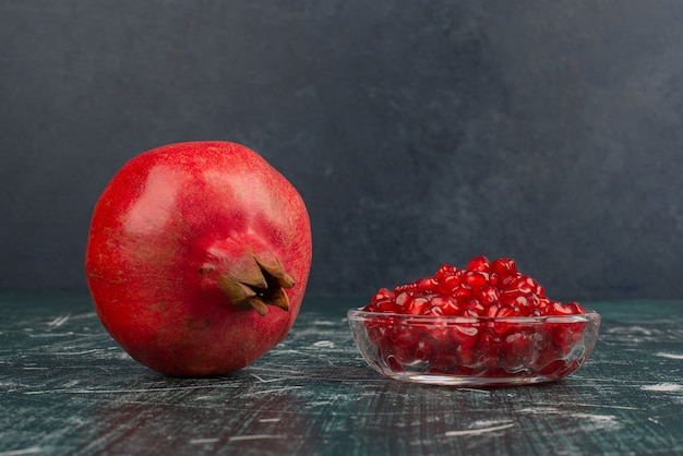 Whole pomegranate and seeds on marble table.