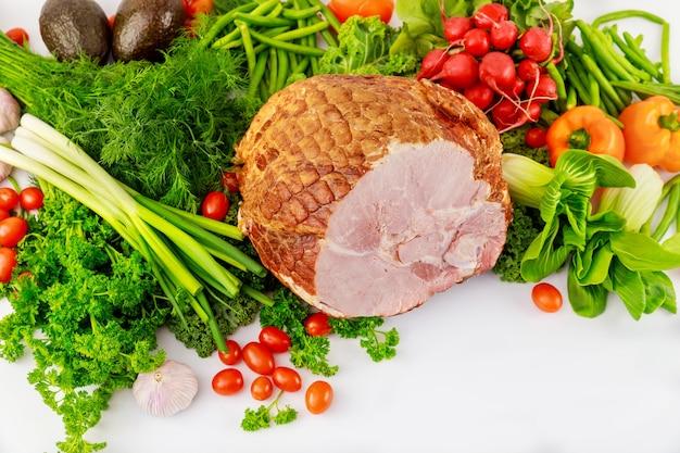 新鮮な野菜を添えた丸ごとポークハム。健康食品。イースターの食事。