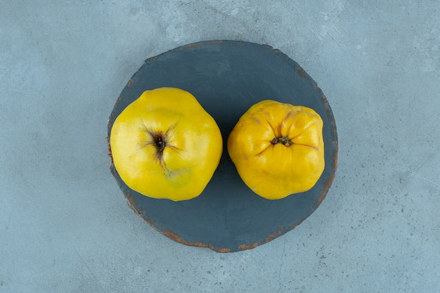 Whole quinces on a board , on the marble background. high quality photo