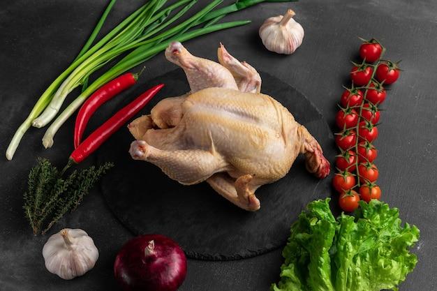 Целое сырое куриное мясо на деревянной разделочной доске, вид сверху