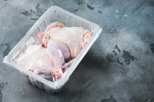 텍스트 복사 공간이 있는 회색 배경에 전체 생 닭고기 패키지