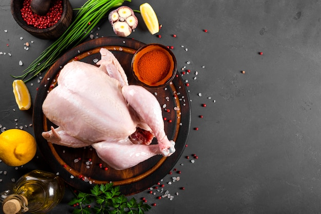 木製のまな板の上に丸ごとの生の鶏肉とそれを調理するための調味料の上面図。