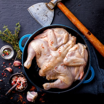 Whole raw chicken with herbs and spices on a frying pan