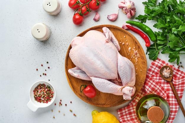 Целая сырая курица с ингредиентами для приготовления розового перца, лимона, тимьяна, чеснока, щавеля из помидоров черри и соли на кухне на светло-сером фоне из сланца, камня или бетона. вид сверху с копией пространства.