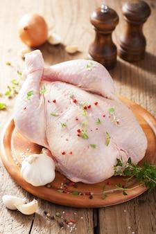 Цельная сырая курица с розовым перцем и тимьяном
