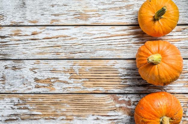 Whole raw orange pumpkins. white wooden background