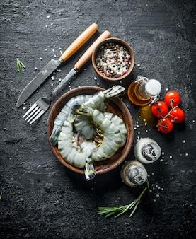 Целые сырые креветки в миске с помидорами и специями. на черном деревенском