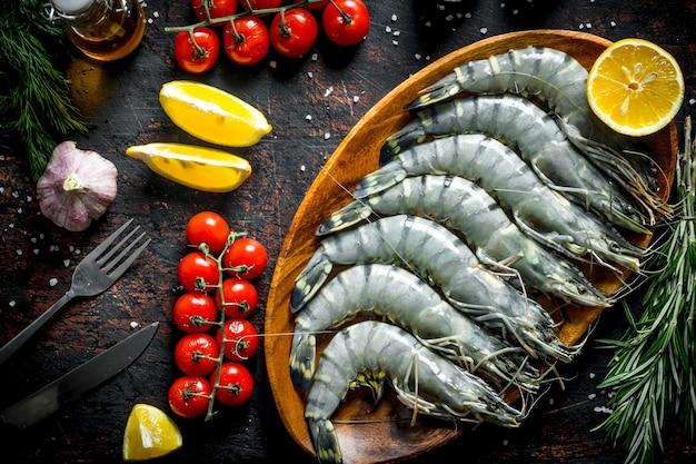 Целые сырые креветки с розмарином, помидорами и лимоном.