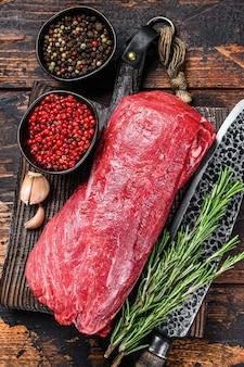 정육점 칼로 나무 커팅 보드에 스테이크 필렛 미뇽에 대한 전체 원시 안심 송아지 고기.